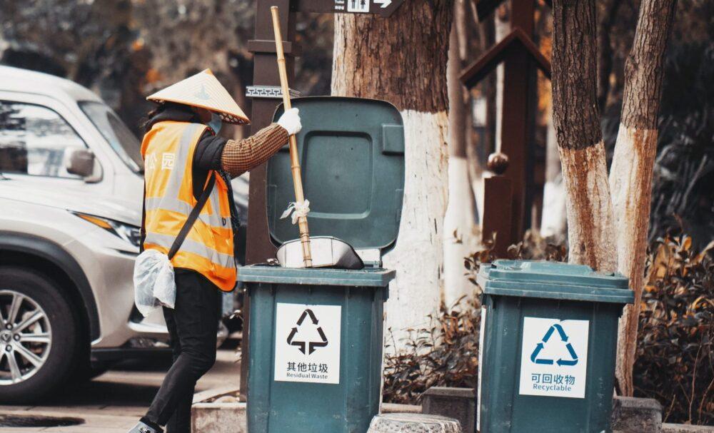 man in yellow jacket and black pants standing beside trash bin