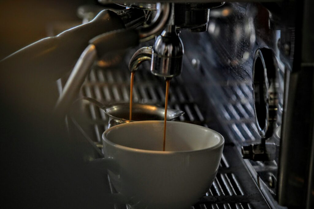 Espresso dripping into a porcelain mug from a steel machine