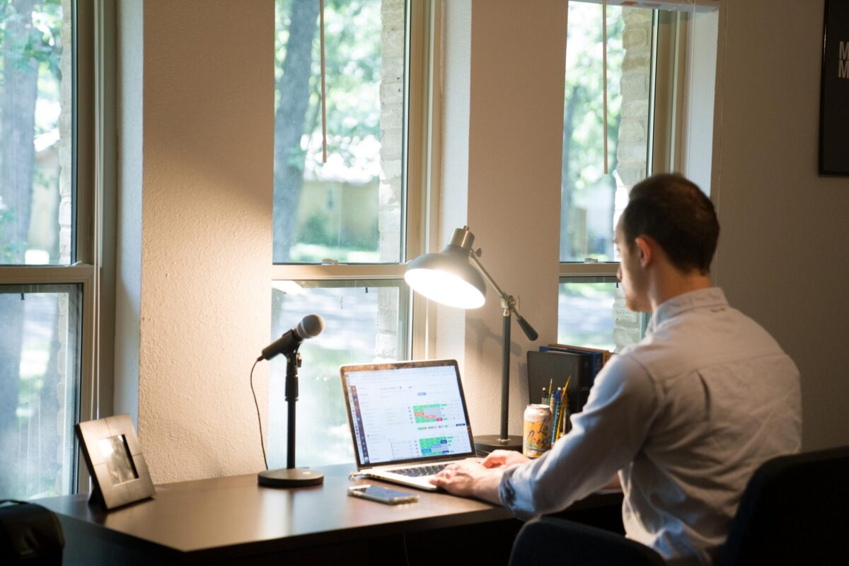 man in white dress shirt sitting on chair using laptop computer