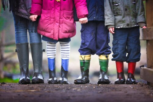 four children standing on dirt during daytime