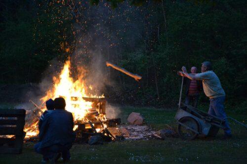 man in blue shirt sitting on black camping chair near bonfire during nighttime