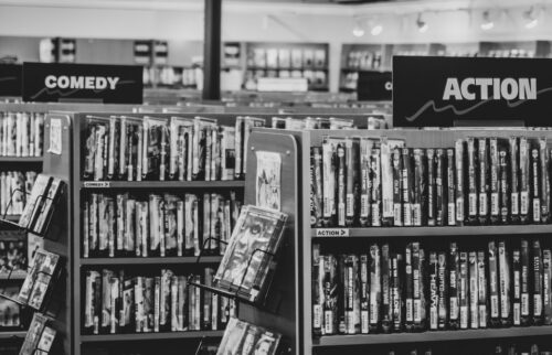 grayscale photo of books on shelves