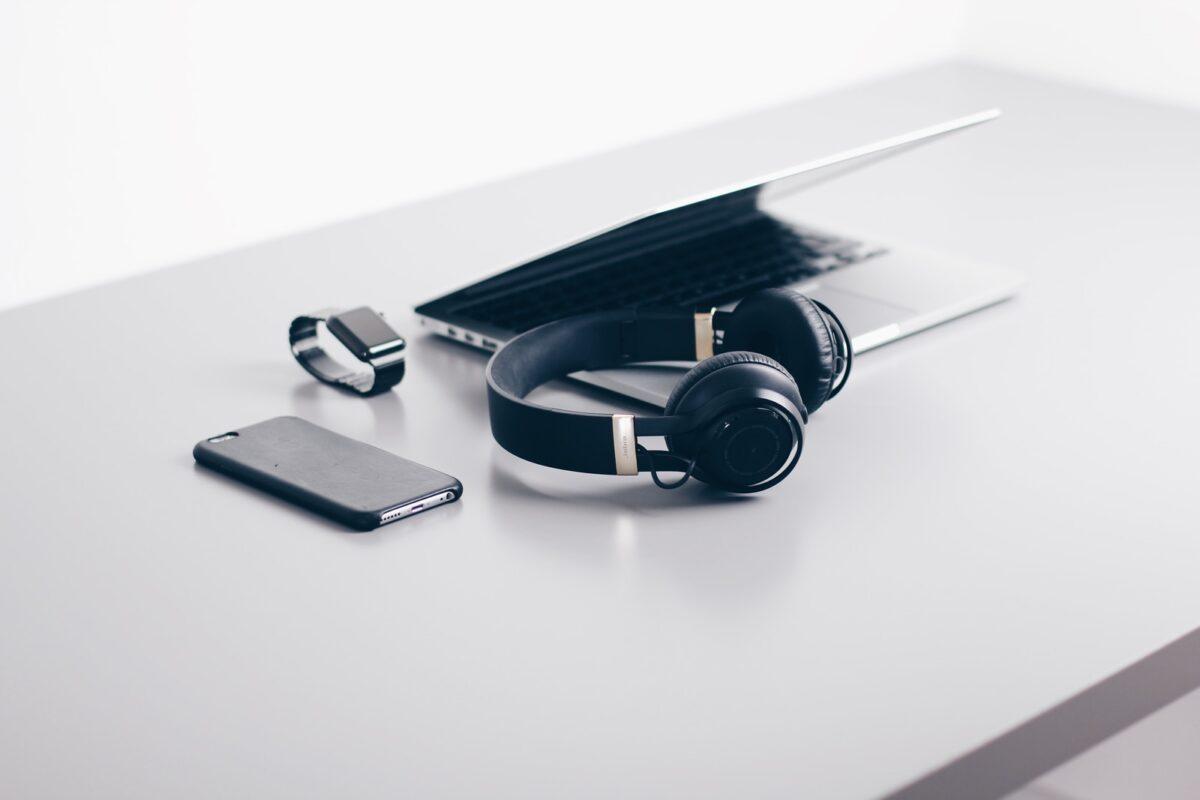 black cordless headphones beside closed black laptop computer and smartphone