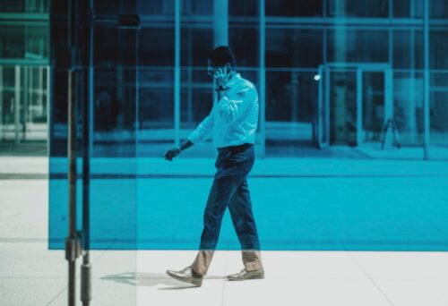 man in blue dress shirt and black pants standing on blue floor
