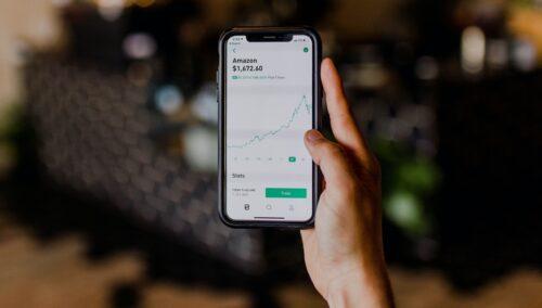 person holding black iPhone displaying stock exchange